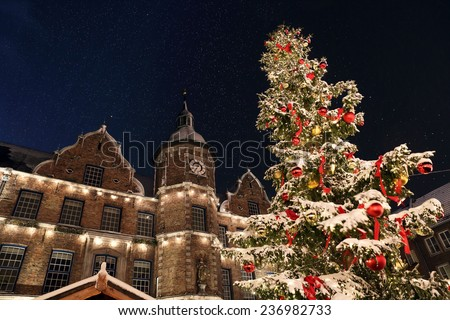Spectacular view on the D�¼sseldorf town hall and Marktplatz Christmas market with a snowcapped Christmas tree. The picture was taken during light snowfall with a sensational night sky. - stock photo