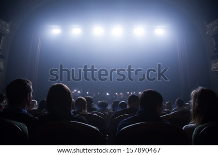 Spectators wait for the start of the concert sitting in the chairs in the auditorium. - stock photo