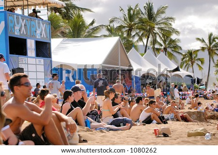 Spectators watch surf competition on Oahu Hawaii's North Shore. (image contains noise) - stock photo