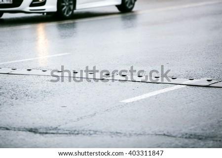 speed bump on wet asphalt road - stock photo