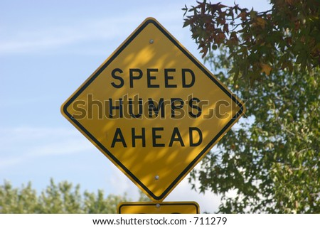 Speed hump sign in the shade - stock photo