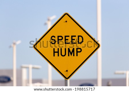 Speed hump sign on busy street. - stock photo