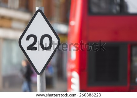 Speed limit sign in a city district with a red blurred bus in the background - stock photo