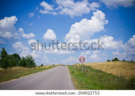 Speed limit 60 sign on rural road. - stock photo