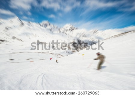 Speed skiing on snowy slope in ski the famous and scenic resort of La Thuile, Aosta Valley, Italy. Radial blurred motion effect applied. Unrecognizable people. - stock photo