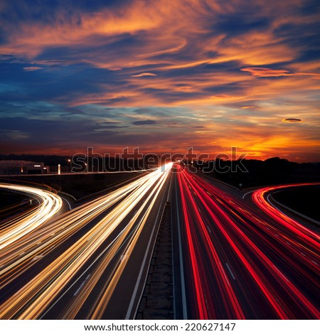Speed Traffic at Dramatic Sundown Time - light trails on motorway highway at night,  long exposure abstract urban background - stock photo