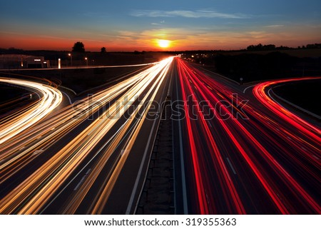 Speed Traffic light trails on highway at sundown time, long exposure, urban background with sun and dark sky - stock photo