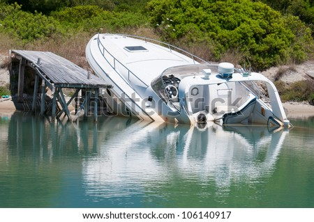 Speedboat beached and partially sunk at it's mooring - stock photo