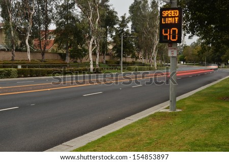Speeding cars and traffic warning sign/Traffic Speed Zone.Illuminated traffic speed warning sign with speeding cars - stock photo