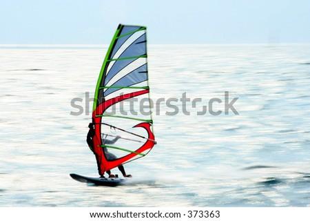 Speeding surfer against reflecting water - stock photo