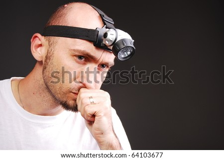 Speleologist with a head lamp on a gray isolated background - stock photo