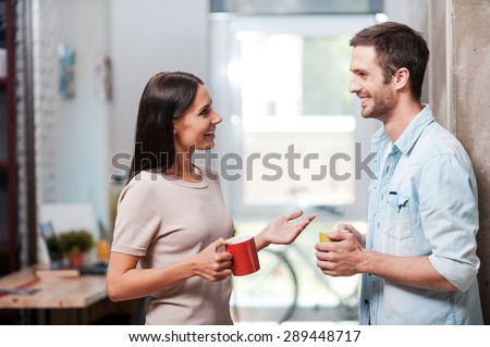 Spending a nice coffee break. Two cheerful young people holding coffee cups and talking while standing in office  - stock photo