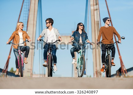 Spending carefree time together. Four young people riding bicycles along the bridge and smiling - stock photo