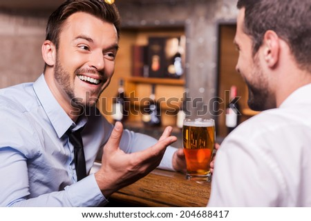 Spending Friday night in bar. Two happy young men in shirt and tie talking to each other and gesturing while drinking beer at the bar counter  - stock photo