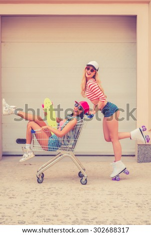 Spending great time together. Side view of cheerful young woman on roller skates carrying her female friend in shopping cart and smiling while skating against the garage door - stock photo