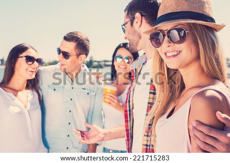Spending great time with friends. Group of young happy people talking to each other while beautiful woman looking at camera and smiling - stock photo