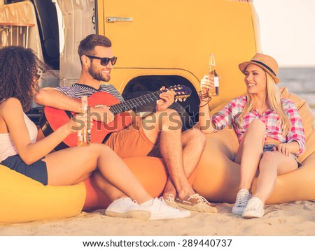 Spending great time with friends. Happy young man playing guitar while two young women sitting close to him and drinking beer with yellow minivan in the background - stock photo