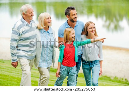 Spending quality time with family. Happy young family walking outdoors together while little girl pointing away and smiling - stock photo