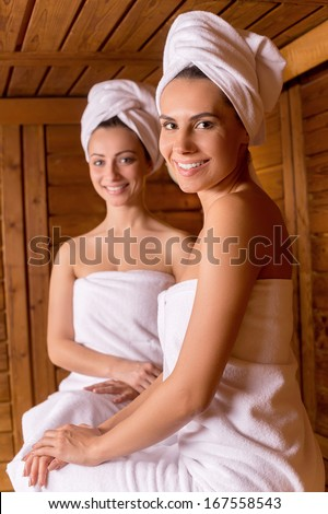 Spending time in sauna. Two attractive women wrapped in towel sitting at sauna and smiling to you - stock photo