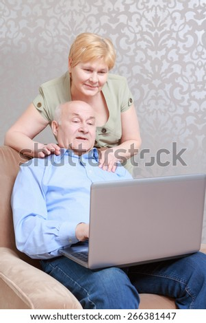 Spending time together. Confident elderly man using a laptop while relaxing in an armchair at home in his living room while his wife embracing him on the shoulders - stock photo
