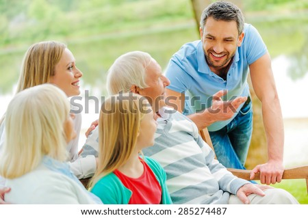 Spending time with family. Happy family of five people talking to each other and smiling while sitting outdoors together  - stock photo