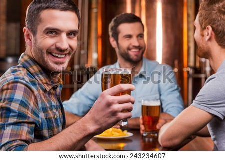 Spending time with friends. Handsome young man toasting with beer and smiling while sitting with his friends in beer pub  - stock photo