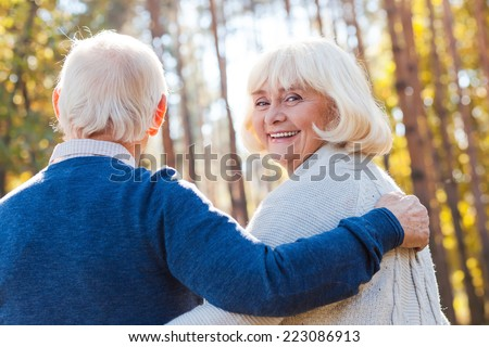 Spending time with husband. Rear view of happy senior woman looking over shoulder and smiling while walking by park with her husband  - stock photo