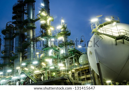 sphere gas tank  and column towers at twilight - stock photo