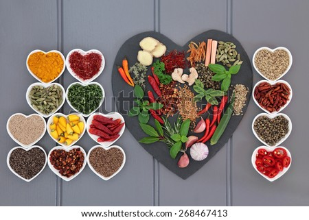 Spice and herb collection on heart shaped slate and in porcelain dishes over wooden grey background. - stock photo