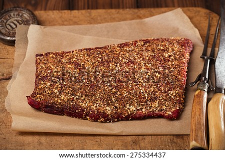 spice rubbed raw  beef fillet, making jerky meat on wooden backdrop with vintage curving fork and knife - stock photo