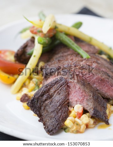 Spice rubbed skirt steak with summer corn succotash, gigante beans, chorizo and scallions  - stock photo