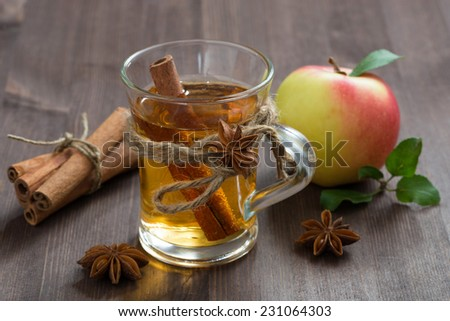 spiced apple cider and spices on a wooden table, close-up - stock photo