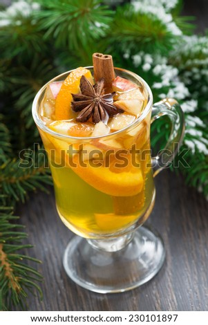spiced apple cider in a glass on a wooden background, vertical - stock photo