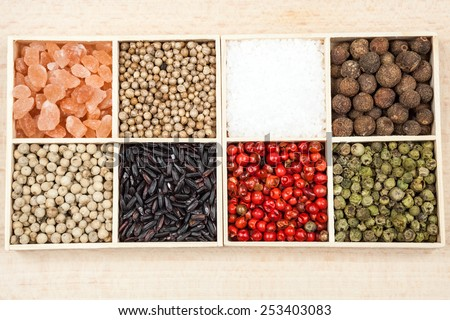 Spices and black rice in a wooden box: himalayan salt, sea salt, white, green and red pepper, allspice and coriander - stock photo