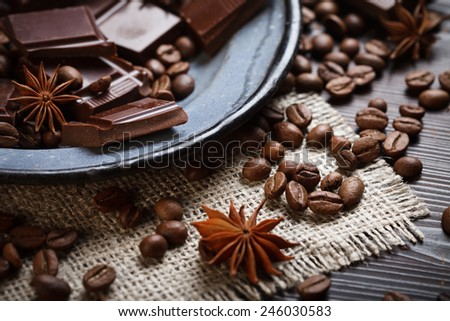 Spices and coffee beans with chocolate on rustic plate - stock photo