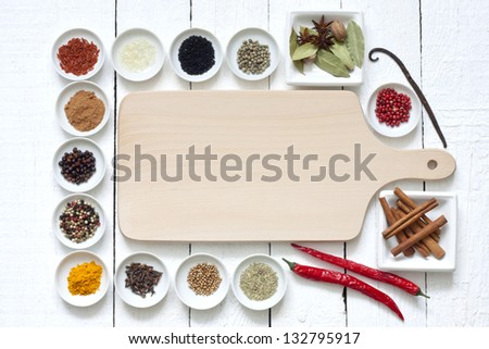 Spices and dried vegetables with cutting board on white planks - stock photo