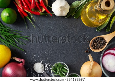 Spices and food ingredients on slate background with copy space - stock photo