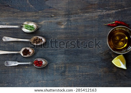 Spices and olive oil. Herbs and spices selection - old metal spoons and rustic wooden background. Cooking, food or health concept. - stock photo