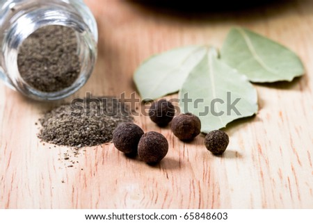 spices: black pepper and bay leaves closeup on wooden background - stock photo