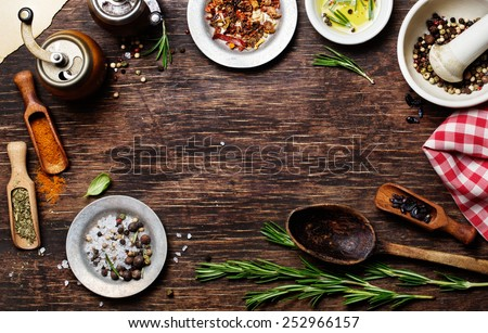 Spices for use as cooking ingredients on a wooden background, with copyspace - stock photo