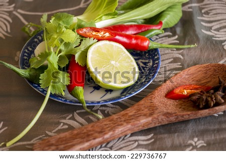 Spices, fresh herbs and lemon in a rustic kitchen ready to be used as cooking ingredients and seasoning with star anise, red hot cayenne chili pepper, assorted fresh herbs and a half a lemon - stock photo