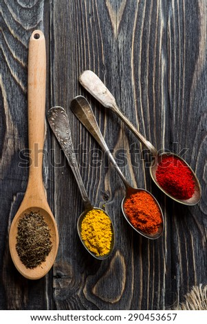 Spices. Herbs and spices selection in old metal spoons over wooden background. Curry, Saffron, turmeric, cinnamon and other. - stock photo