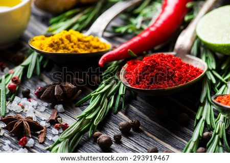 Spices. Herbs and spices selection in old metal spoons over wooden background. Curry, Saffron, turmeric, pepper and rosemary. - stock photo