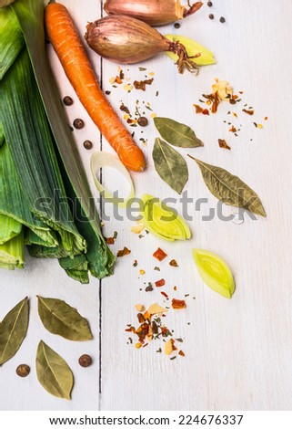 Spices, herbs and vegetables  for soup or broth on white wooden background - stock photo