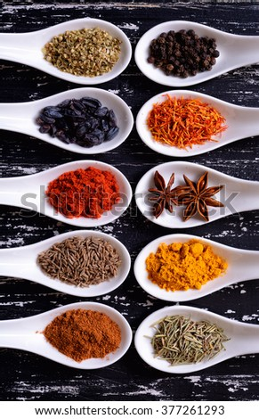 Spices in ceramic bowls on wooden background. - stock photo