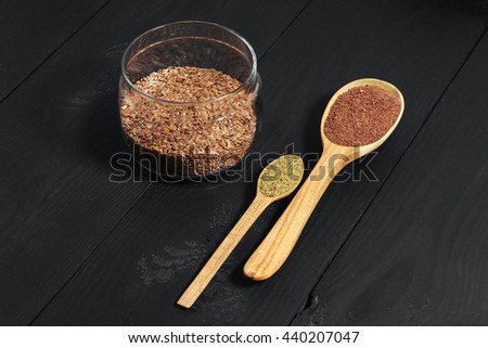 Spices in spoon, linen in glass plate on black wooden background. Close-up - stock photo
