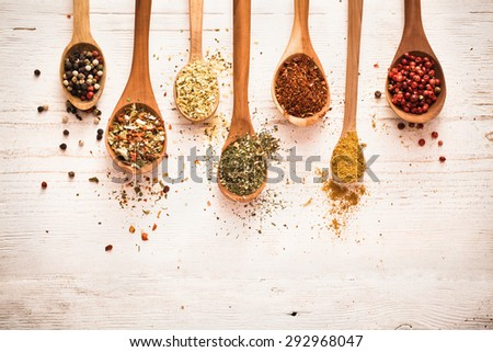 Spices in wooden spoons on white wooden background - stock photo