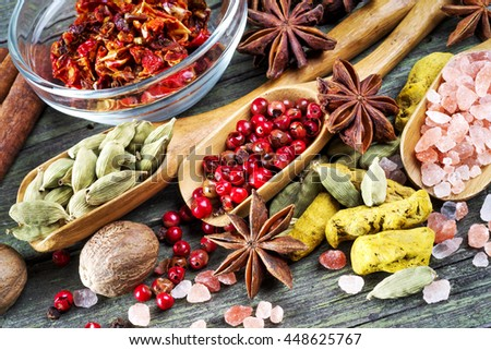 spices on wooden table, aniseed, himalayan salt, cinnamon, red pepper, cardamom, paprika, turmeric and nutmeg, selective focus - stock photo