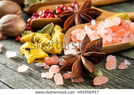 spices on wooden table, aniseed, himalayan salt, red pepper, cardamom, turmeric and nutmeg, selective focus - stock photo