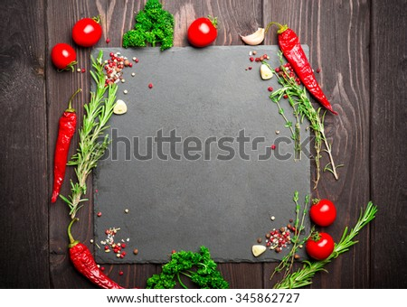 Spices over dark stone background with empty place for text. Red Chilli pepper, tomatoes, pepper corns, rosemary and sea salt. - stock photo